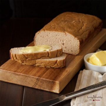 loaf of paleo sweet bread on wooden cutting board with dish of butter and knife
