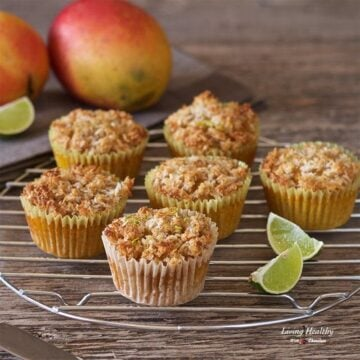mango muffins topped with coconut lime streusel cooling on a round rack with lime wedges and mangos in background