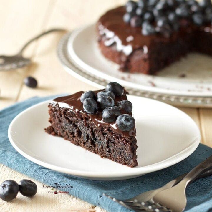 plate with a slice of blueberry chocolate cake topped with fresh blueberries and the full cake in the background