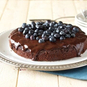 serving plate with a paleo blueberry chocolate cake topped with fresh blueberries and chocolate sauce