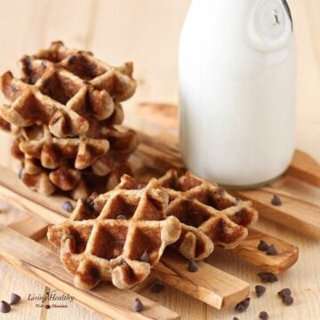 chocolate chip waffles stacked on a slotted tray with a jar of milk in the background