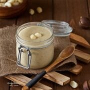 jar of homemade white chocolate macadamia nut butter with small wooded spoon in foreground