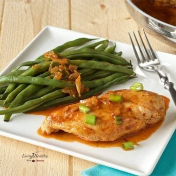 plate of skillet cooked chicken breast with spicy paprika sauce and green beans