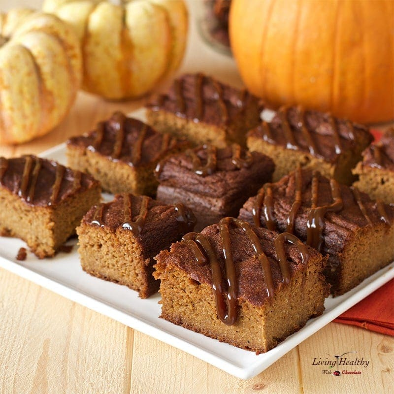 plate with cut squares of paleo marble pumpkin cake drizzled in homemade caramel and small Pumpkins in background