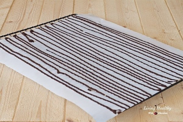 parchment paper covered in rows of chocolate for making chocolate sprinkles