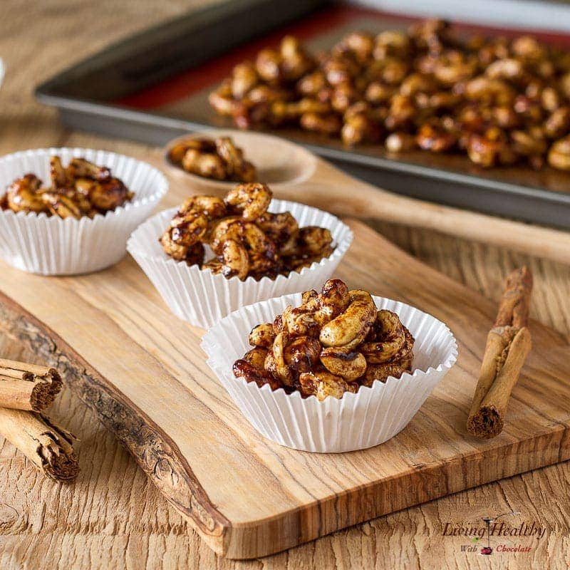 wooden cutting board display with cupcake holders filled with cinnamon sugar cashews and a tray of more nuts cooling behind
