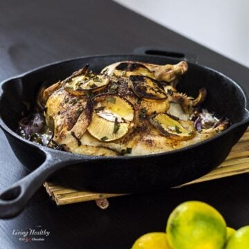 cast iron pan filled with roasted cinnamon lemon chicken topped with slices of lemon and caramelized onion