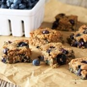 Blueberry bars cut into squares with container of blueberries in background