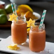 star fruit smoothies with slices of star fruit and straws in glass jars