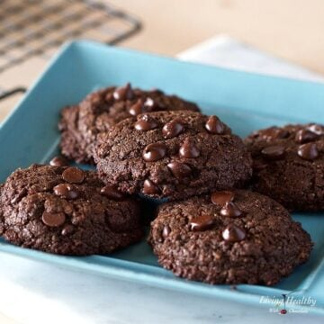 chocolate cookies on a blue plate with cooling rack in background