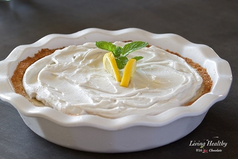 close up of a lemon cream pie topped with whipped cream and two lemon slices