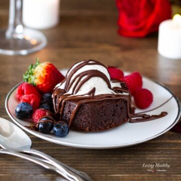 molten lava brownie plated with fresh berries and topped with a scoop of ice cream drizzled with chocolate