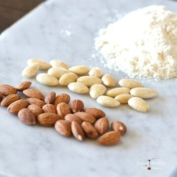 two piles of almonds and one pile of almond flour on a marble table