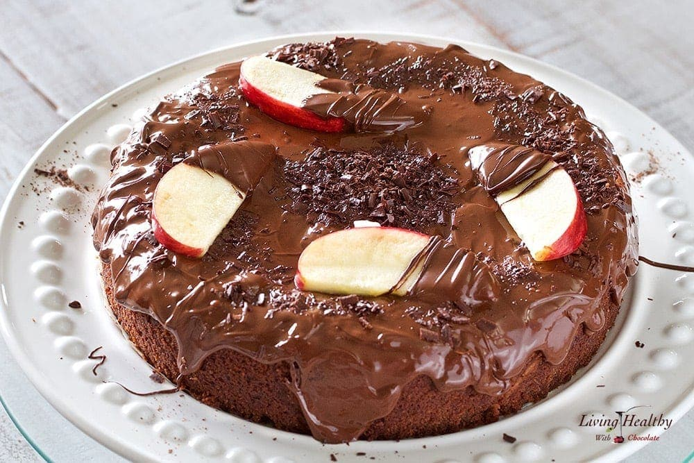 close up of chocolate cake with apple slices and chocolate shavings on top drizzled in chocolate