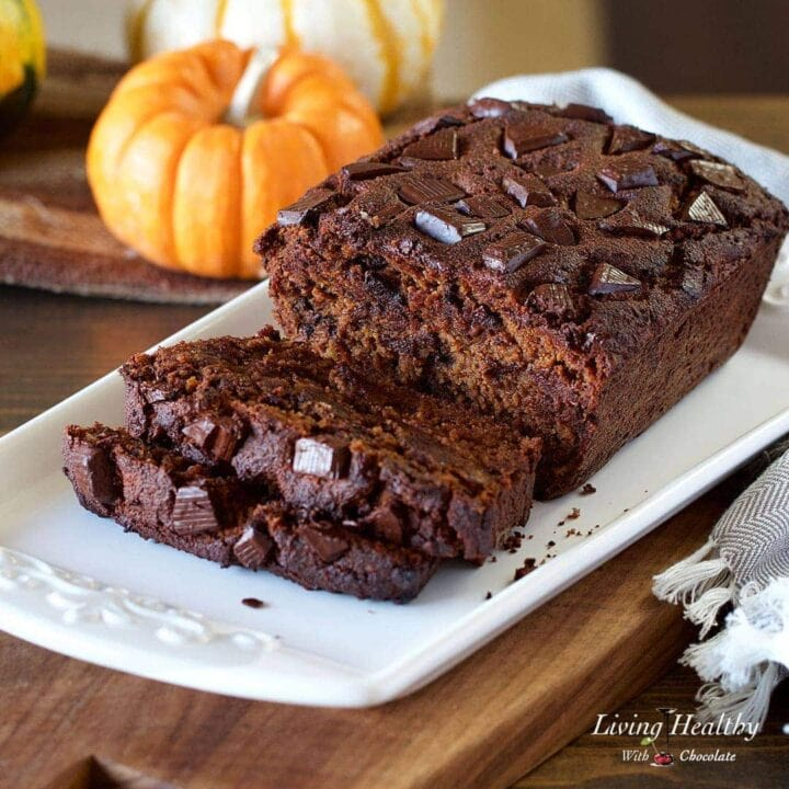 chocolate pumpkin bread displayed on a white serving dish with chocolate chunks on top of the bread