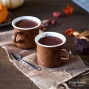 two cups of pumpkin hot chocolate sitting on a table in brown mugs with holiday decorations in the background