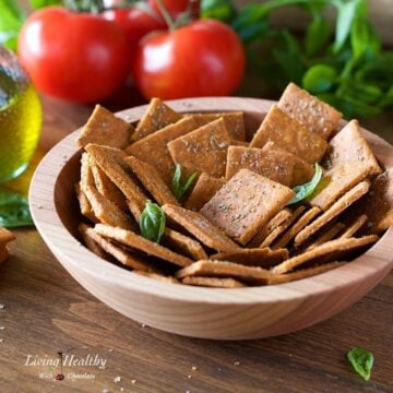 A bowl of crackers made with cassava flour on a table with tomatoes, olive oil and basil in the background