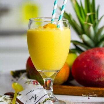 Glass of mango smoothie with two blue straws, plate of mango and pineapple behind the glass