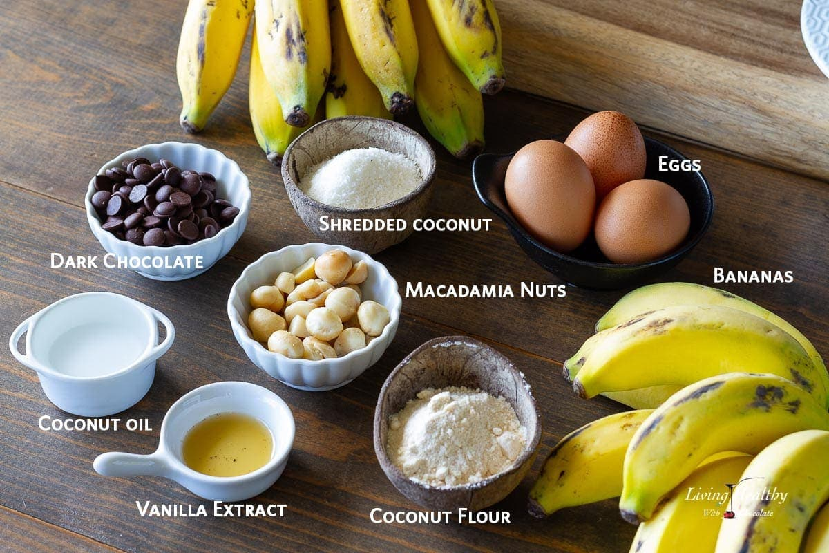 ingredients used to make coconut flour banana muffins displayed on wooden table in a variety of dishes and clearly labeled