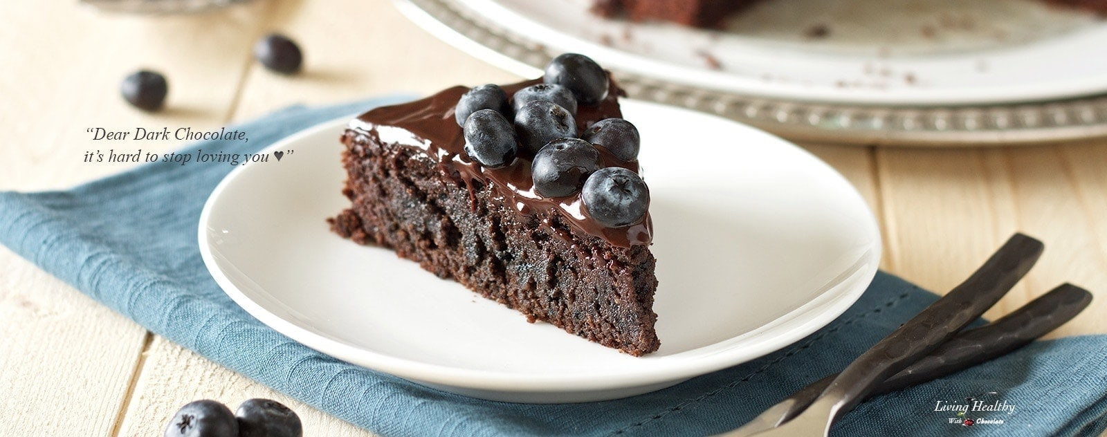 Chocolate cake with blueberries on top on a white plate