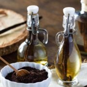 two bottles of vanilla extract and a bowl of vanilla powder on a napkin