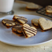 heart shaped vanilla sandwich cookies with chocolate filling inside and a drizzle of chocolate on top