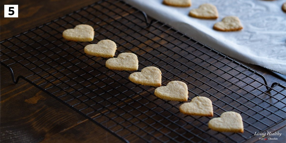 recipe step 5 heart shaped cookies cooling on black wire rack
