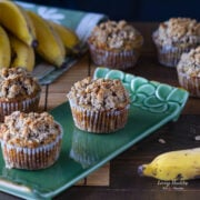 six banana muffins with crumb topping on a table and green plate around some yellow bananas