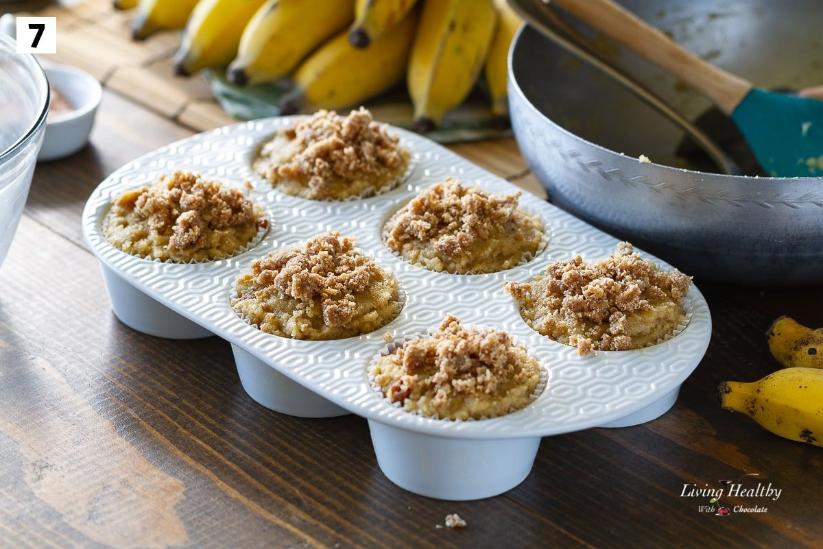 6 cups white ceramic muffin pan filled with batter and a crumb topping
