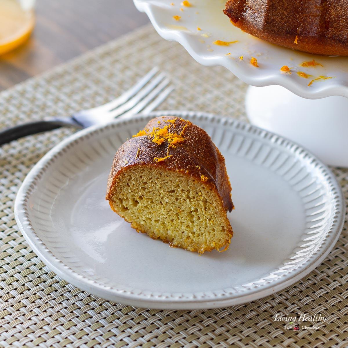 slice of bundt cake on a white place sprinkles with orange zest