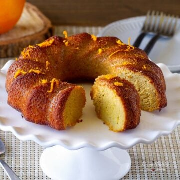 orange cake on stand with a slice in the middle showing the inside