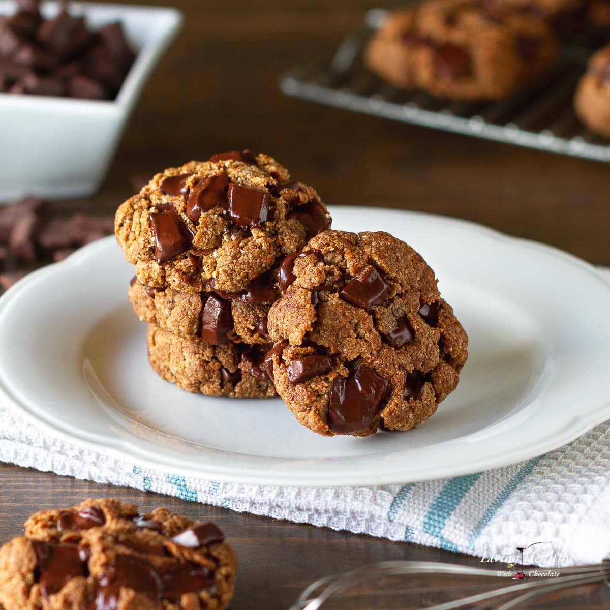 four cookies with large chocolate chunks stacked on a white plate